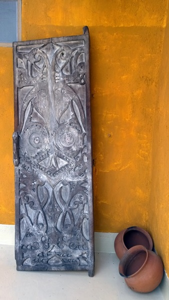 A Dayak door with resident spirit and two pots by the pool