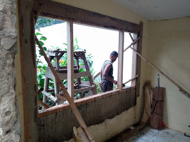 Pak Rojak installing the window frame in the Writer's room
